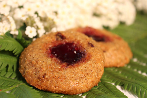 Two gluten free and vegan cherry vanilla cookies with cherry jam centers on a green fern in front of small white flowers