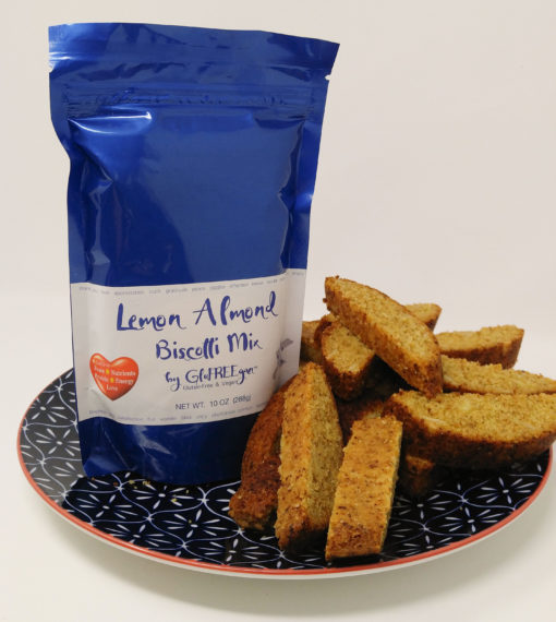 Blue bag of gluten free and vegan lemon almond baking mix next to a pile of biscotti on a blue plate