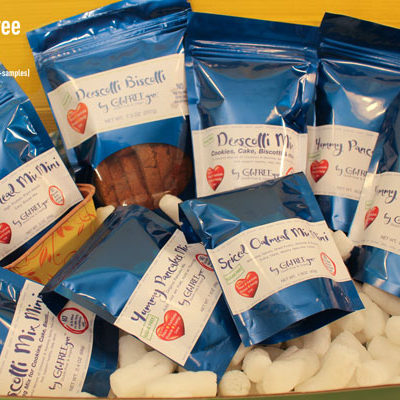 Blue packages of gluten free, sugar free and vegan baking mixes and biscotti piled on top of packing peanuts in a box