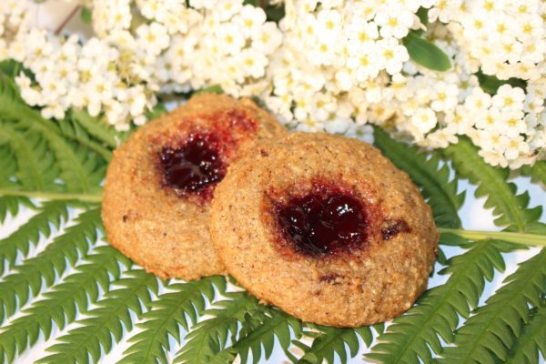 Gluten free, vegan cherry vanilla jam filled cookies sitting on ferns in front of white flowers.