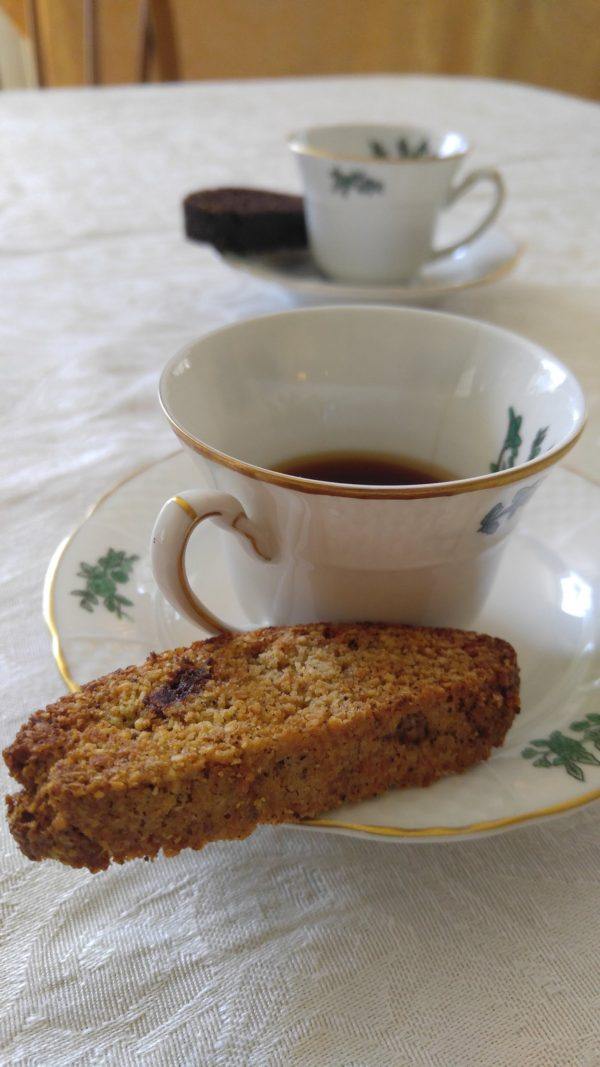 Gluten free and vegan cherry vanilla biscotti on a saucer with a cup of coffee