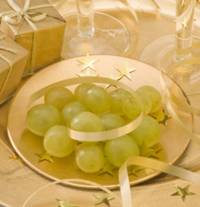 Two glasses of champagne with twelve grapes of luck and New Year's Eve decoration