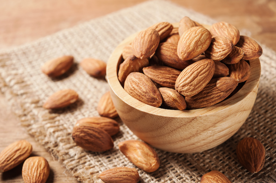 Almond snack fruit in wooden bowl on wood table background in still life style
