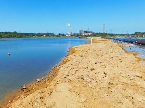 Geotextile tube wall being installed along the perimeter of the coal ash pond
