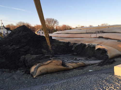 Dewatered material being excavated and loaded for off-site disposal