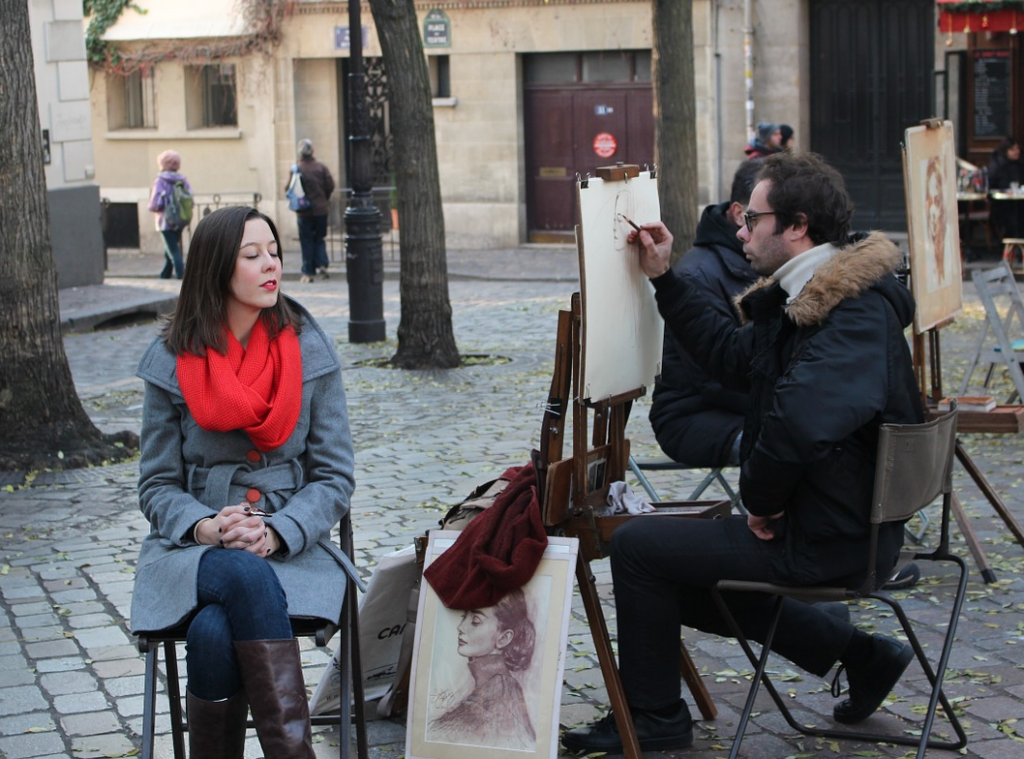 An artist paints a portrait for a tourist in modern-day Montmartre. Photo by stinne24.