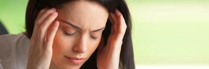 Woman holding sides of her head in pain