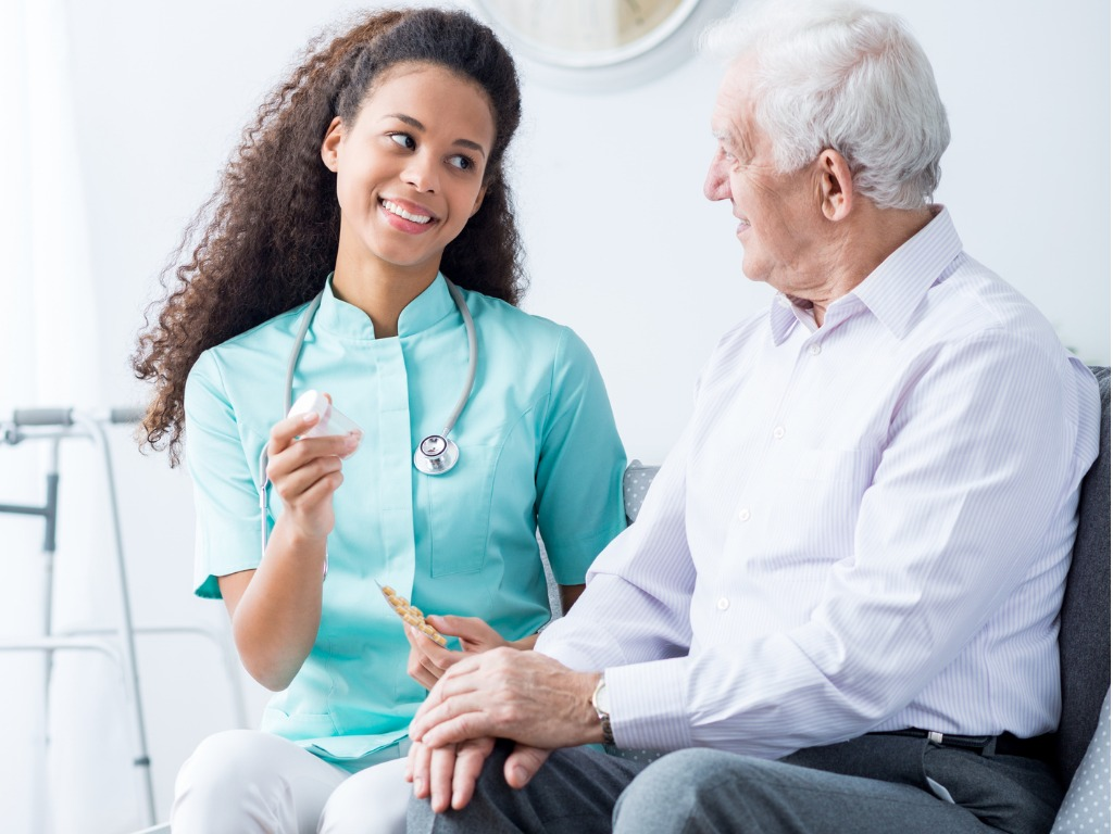 Private Aide helps elderly man to understand his medications.