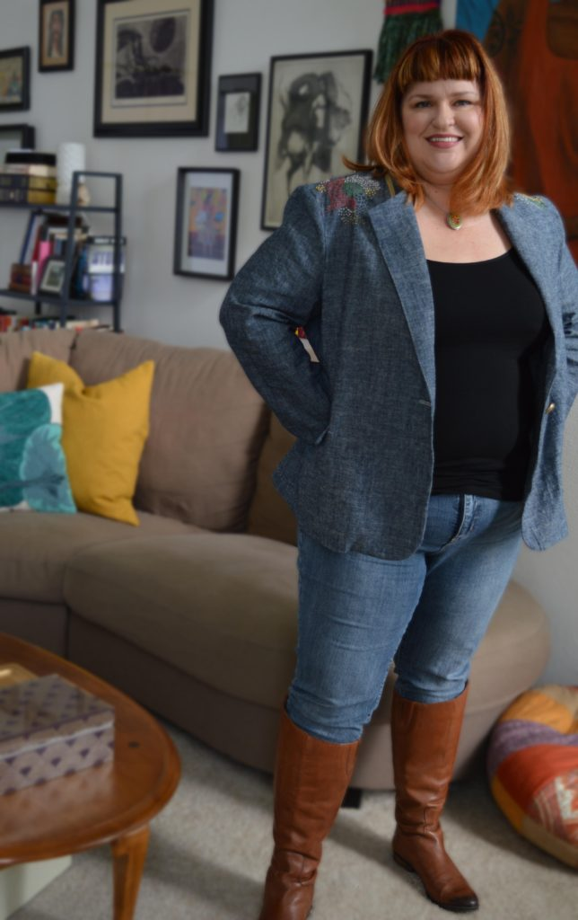 woman wearing a blue blazer from a sewing pattern in linen standing in a living room