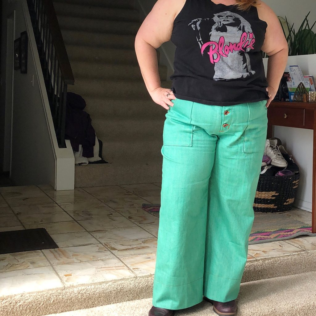 Lauren wearing green denim Lander Pants with a black Blondie tank top standing on a entry landing with hands on hips.