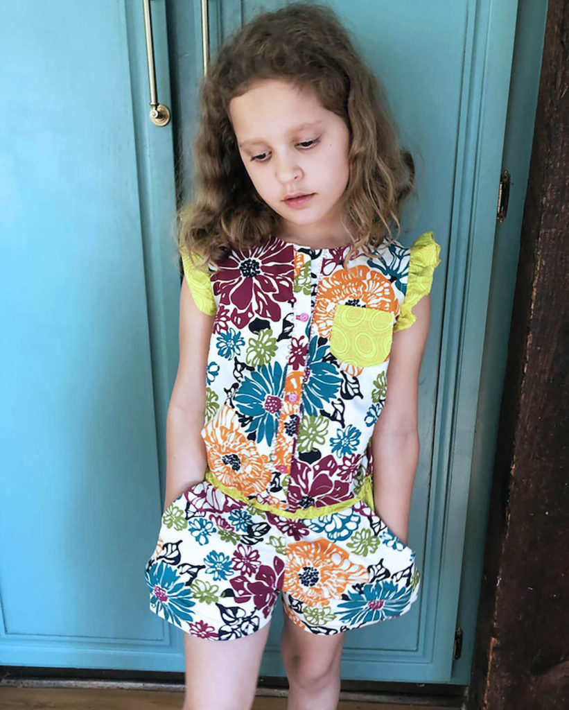 Image of young child in a floral jumpsuit with lime green pocket and shoulder ruffles in front of a blue green cabinet.