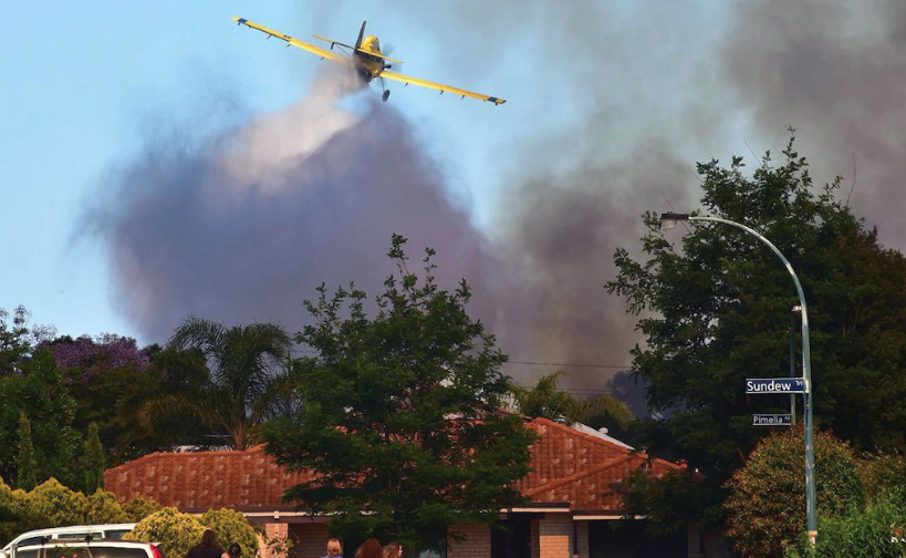A water bomber flies over the bush fire near Glen Iris homes on Saturday.Picture: Chris Morris