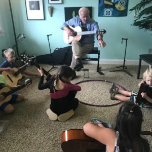 Small children learning guitar