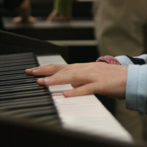 child's hands on a piano keyboard