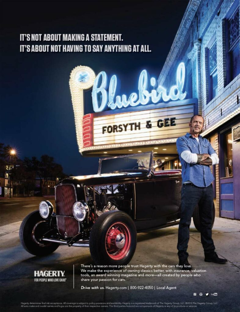 Man with classic car in front of theater marquee