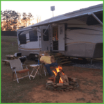 Relaxing by the Campfire Next to the Camper
