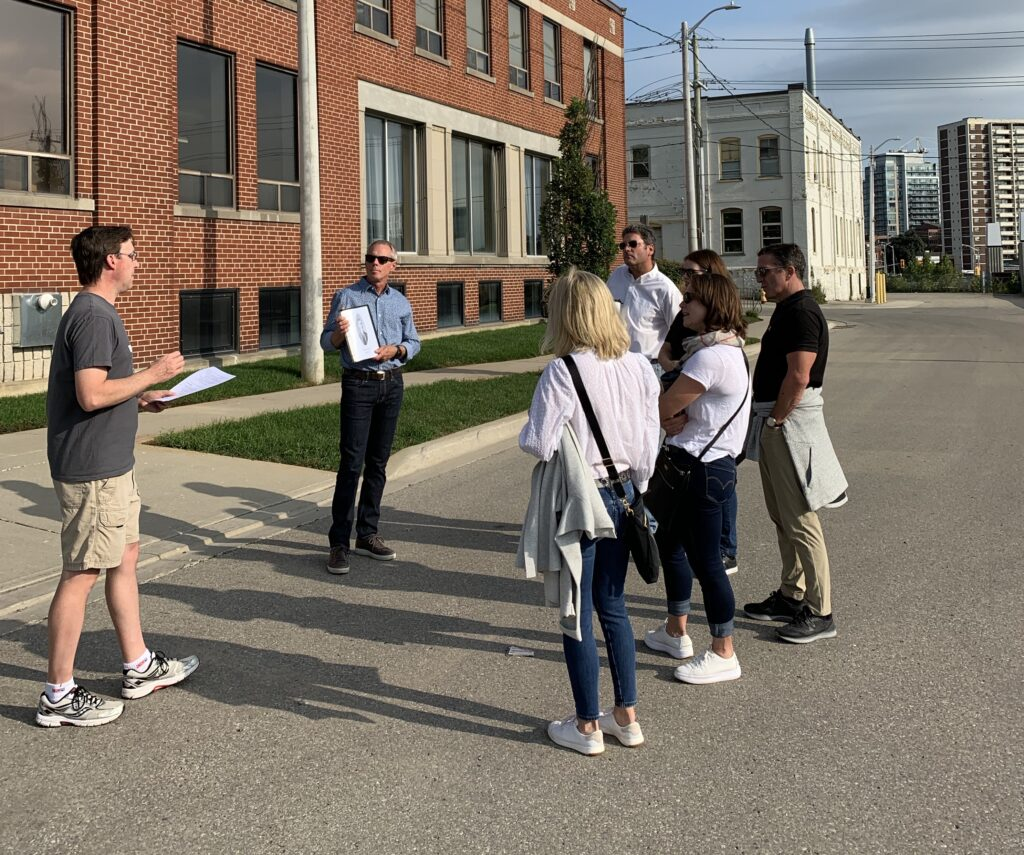 Group of six people on a Stroll Walking Tour facing the guide, Todd Bowman, who is speaking to the group in front of a red brick building in Kitchener's Midtown neighbourhood