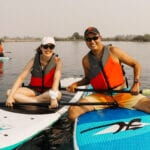 Vanessa and her husband float together sitting on paddle boards