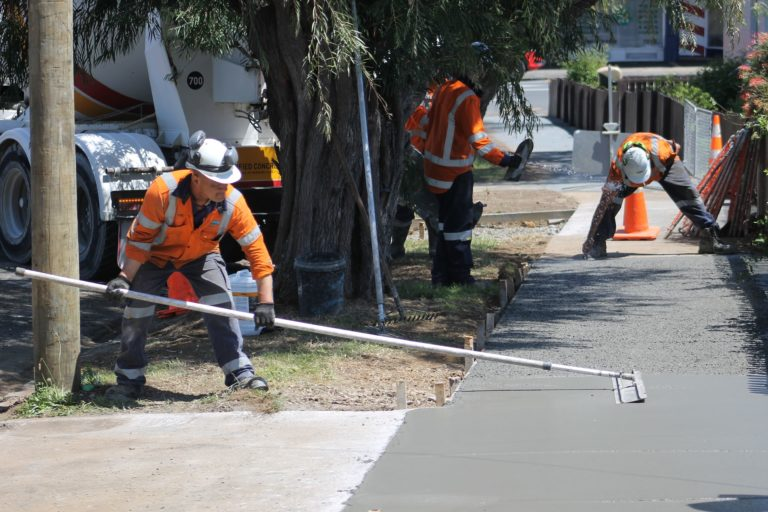 A photo of workers smoothing concrete.