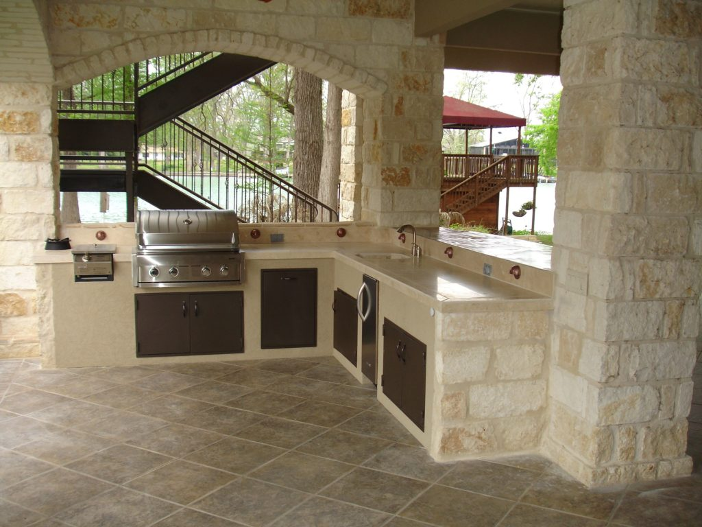 A photo of a beige outdoor kitchen including sink and grill.