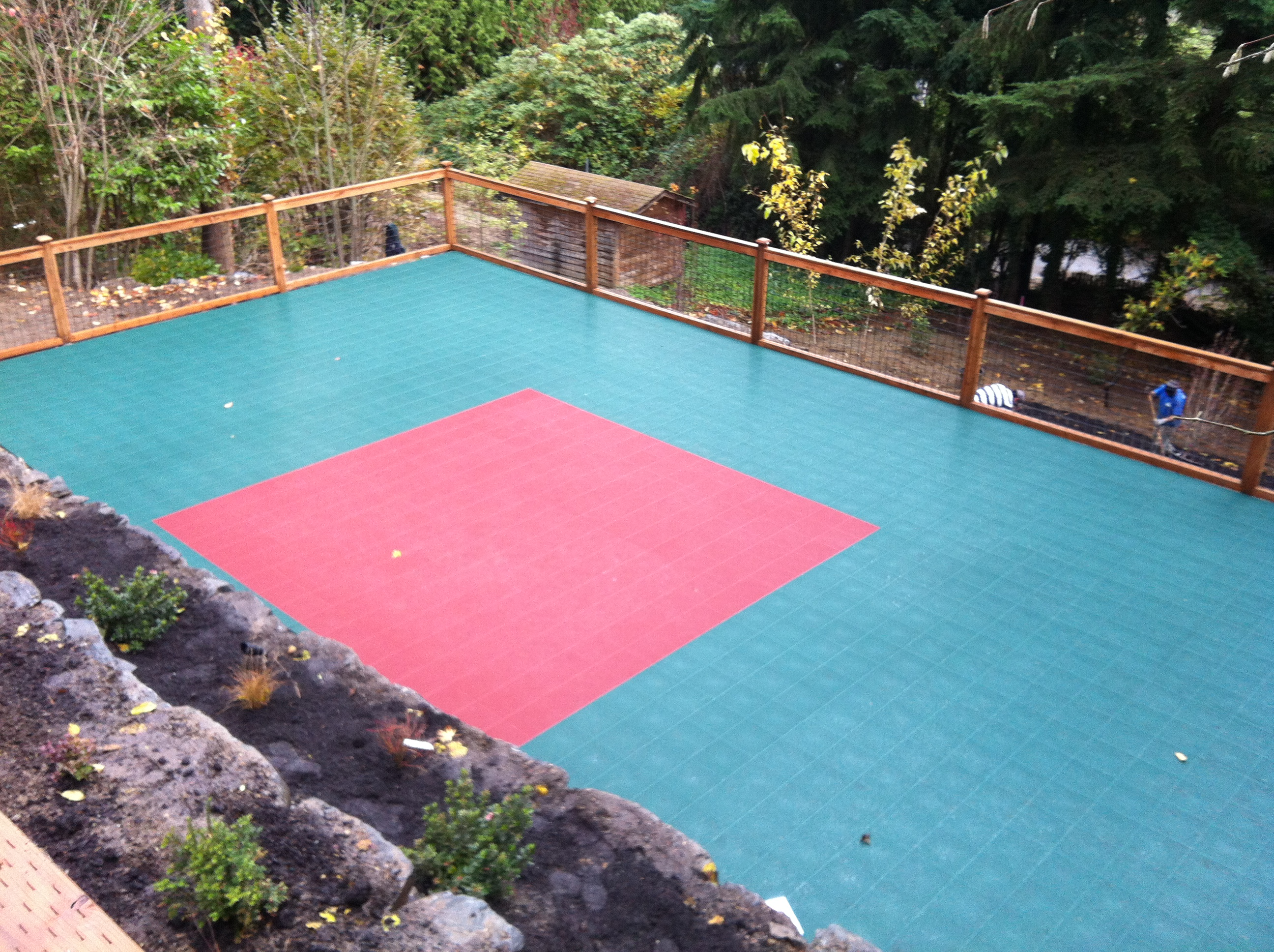 A photo of a backyard Athletic Courts in red and green.