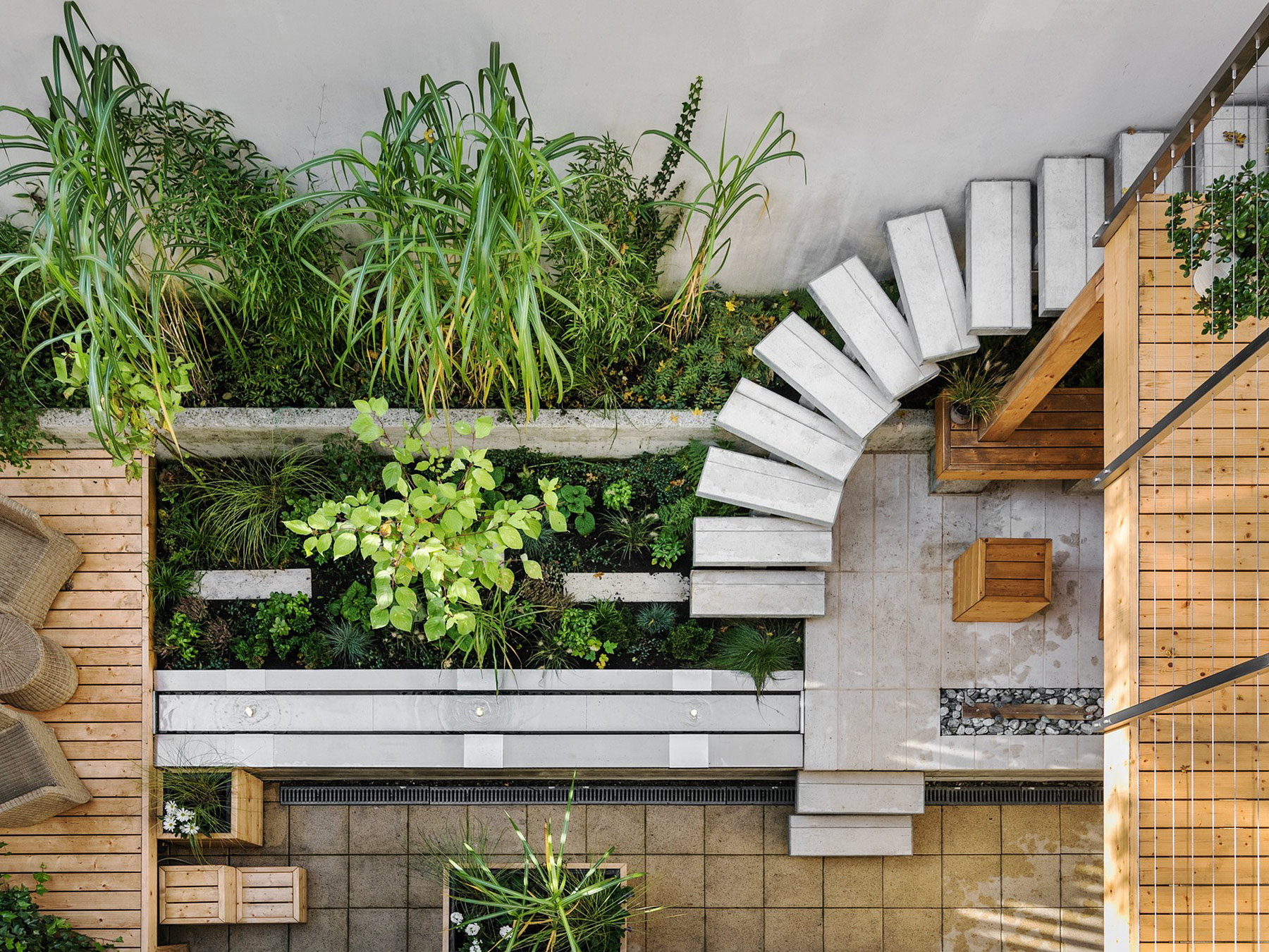 Overhead view of a patio space with greenery, brushed concrete, and wood.