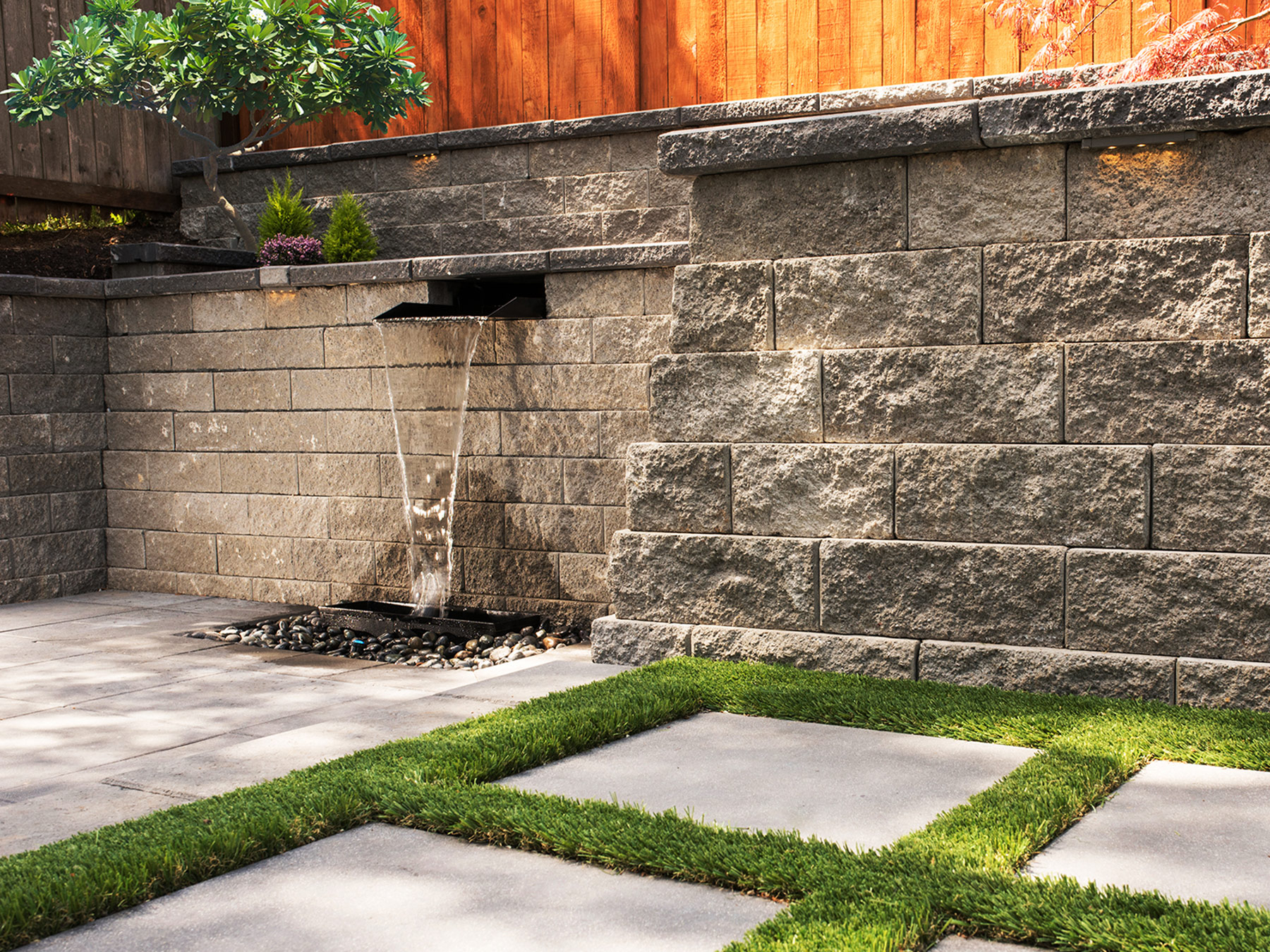 A photo of a backyard with a retaining wall, cement pavers, and a running fountain.