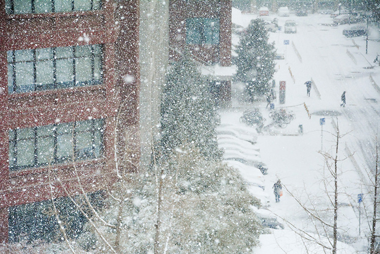 side of red building in snow with people walking below