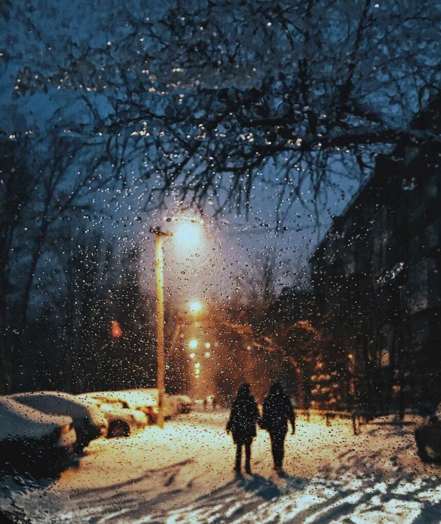people walking in snow under lights
