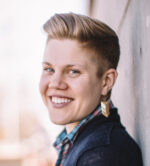 Image description: Will R. Logan, a white, nonbinary/trans person with short blond hair and blue eyes, is outside on a bright day. Will is wearing a navy sweater, plaid button-down shirt, and gold earrings. They are leaning against a wall, head turned towards the viewer, with a big, friendly smile on their face.