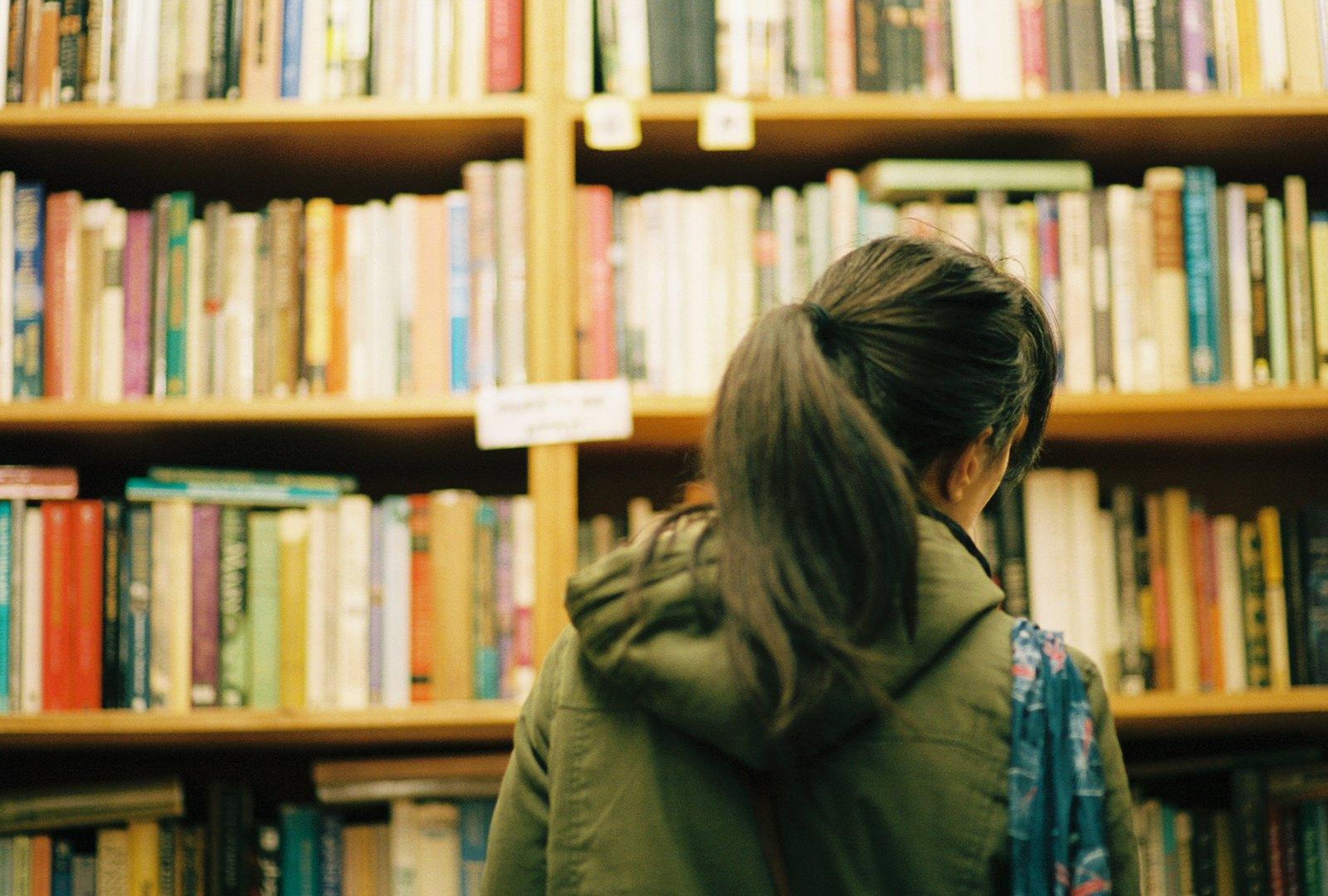 A girl peruses shelves of books