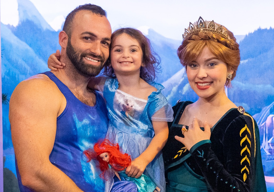 A man and his daughter pose with a Disney princess