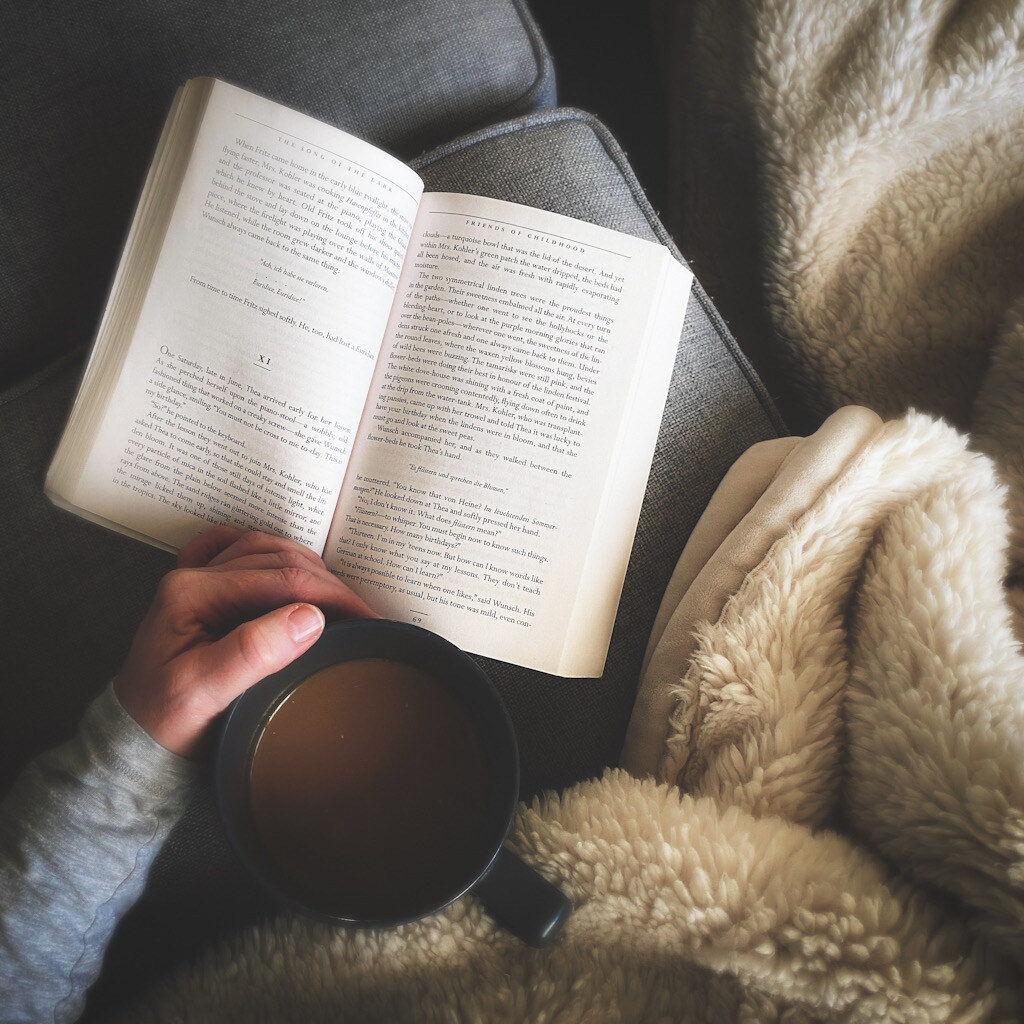 An open book next to a blanket and a person's hand holding a cup of tea