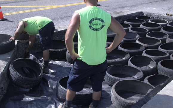 Placing tire cylinders to repair the massive pothole on University Town Center Drive.