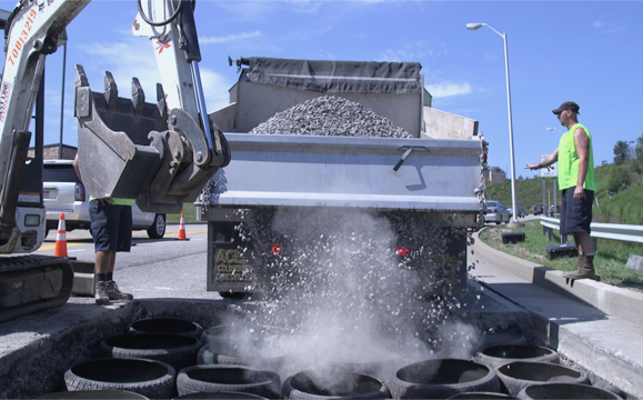 Dumping gravel into the cylinders on University Town Center Drive.