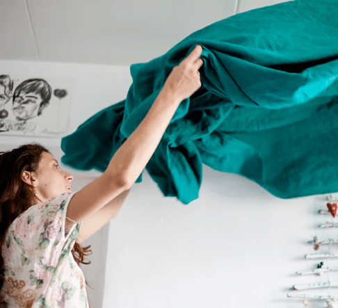 Woman making bed with teal blankets