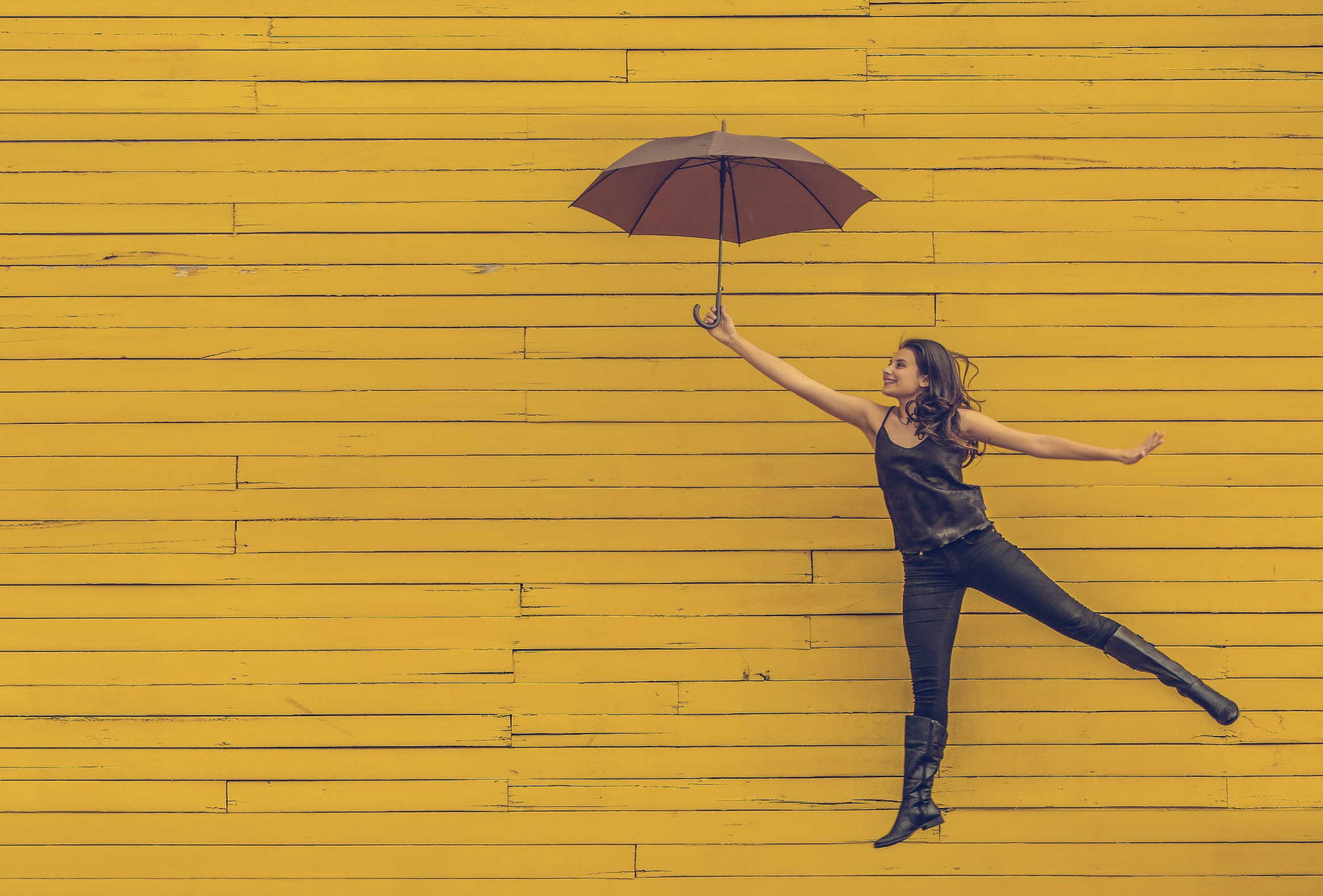 Cultivating Happiness image jumping with an umbrella