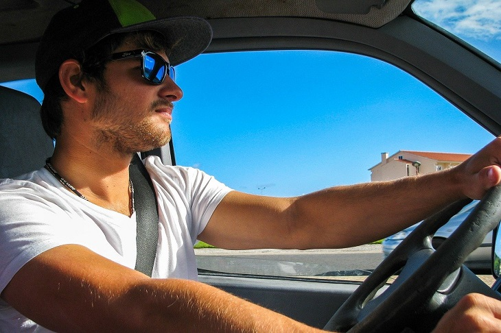 man driving with sunglasses on during summer
