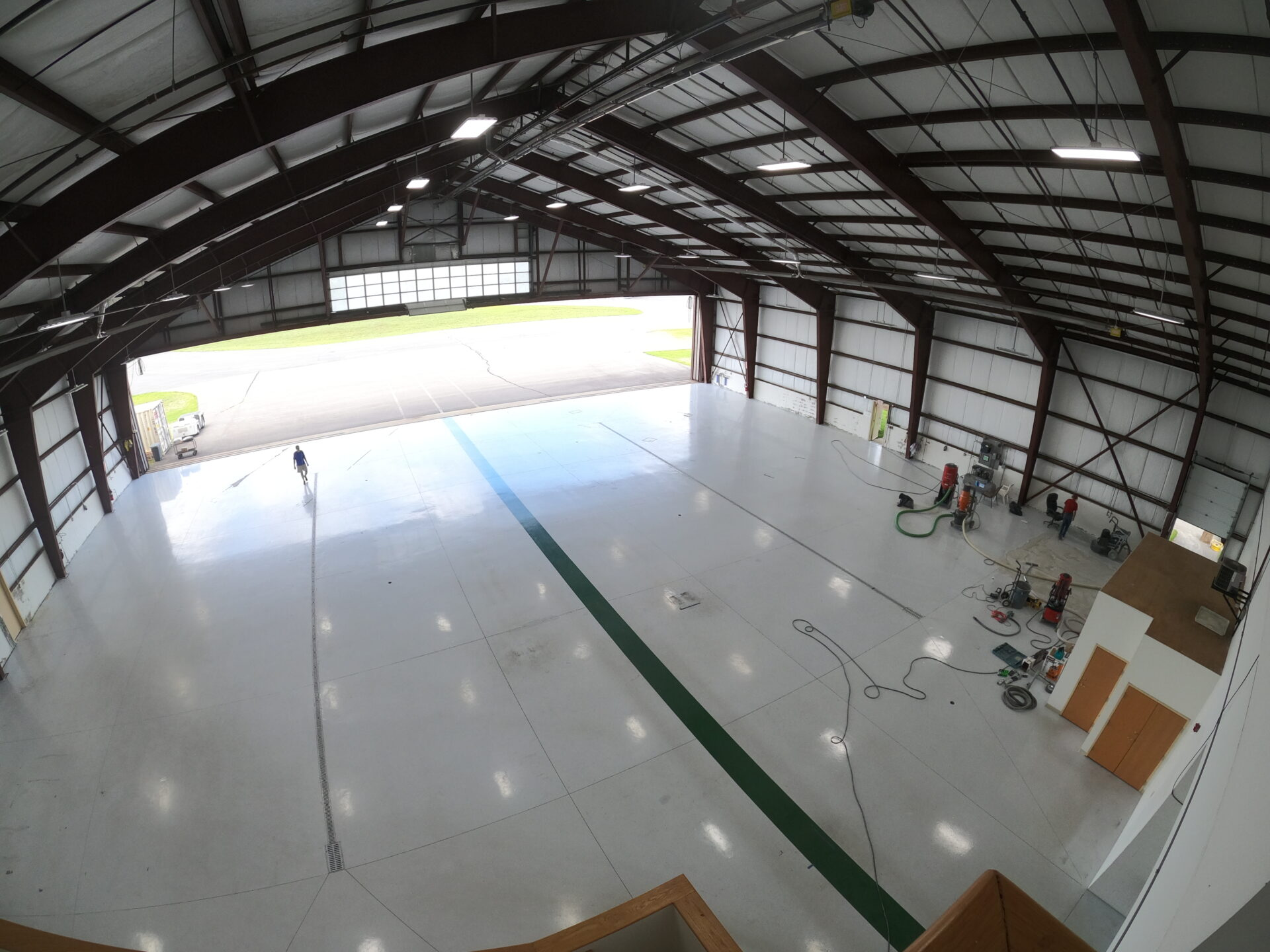 A before and after of an epoxy removal job in Nashua, New Hampshire in an aircraft hangar.