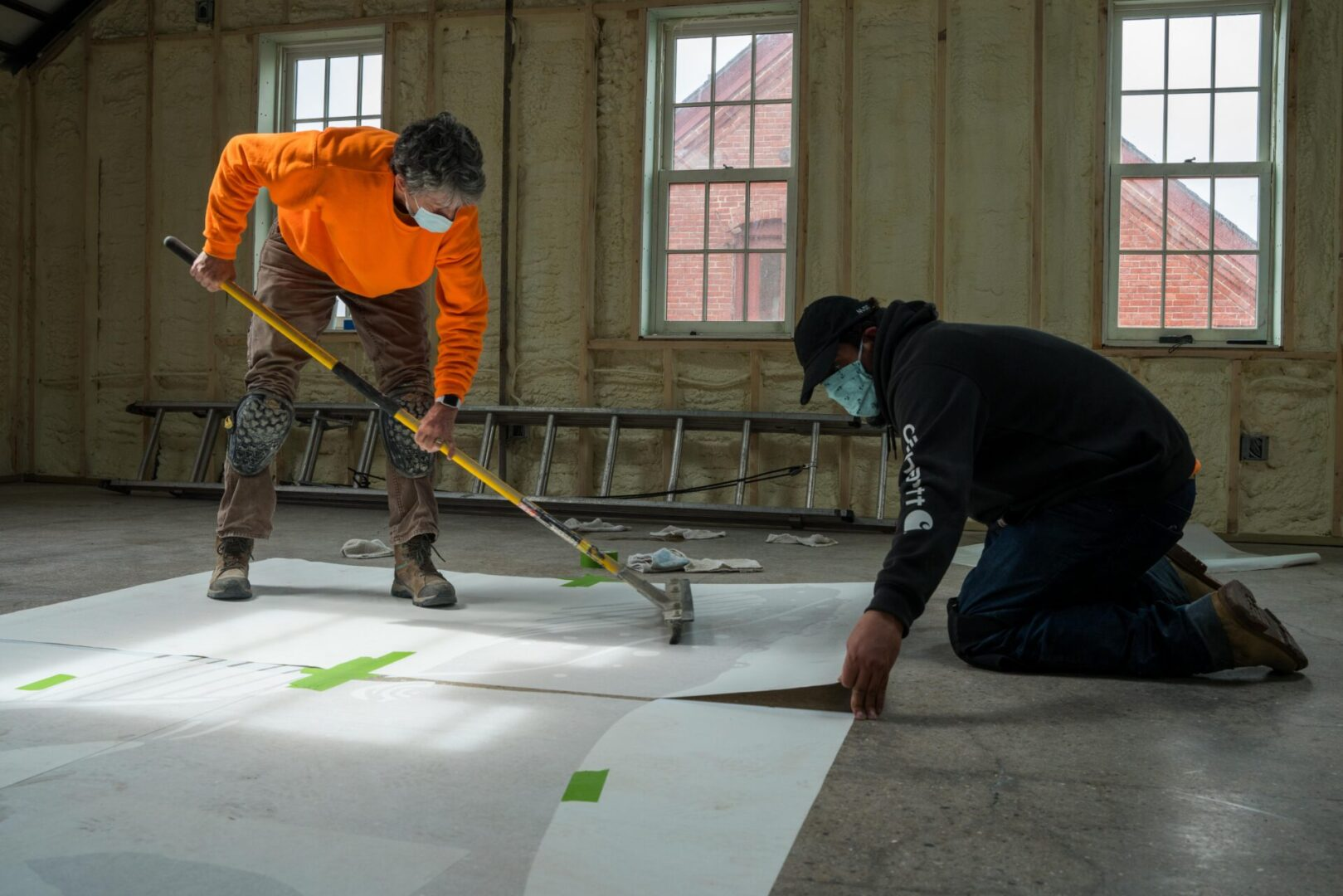 Laying down the stencil for Ocean Aliance. Members of Reliance Concrete & Floormaps lay the stencil