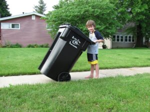 young boy carrying trash outside