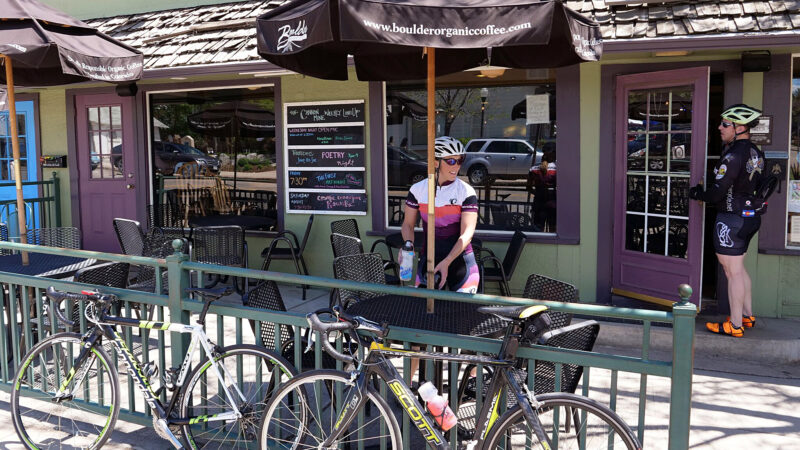 Two cyclists visit a coffee shop in Lafayette, Colorado, the small town that where Cannon Trail was built; a good example of small town residential infill.