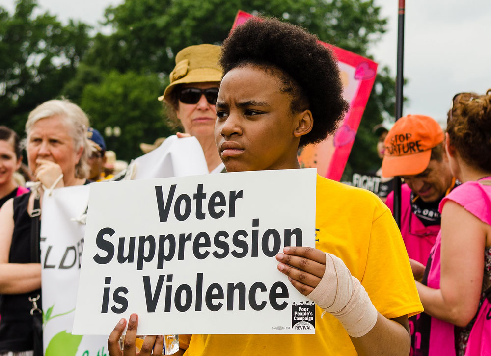 """Black woman at a protest carrying a sign with the text, """"Voter suppression is violence."""""""