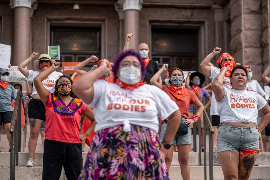 """Pro-choice protesters stand in front of the Texas State capitol with their right fist up in the air, and some of them were a white t-shirt with orange text that says, """"Bans Off Our Bodies."""""""
