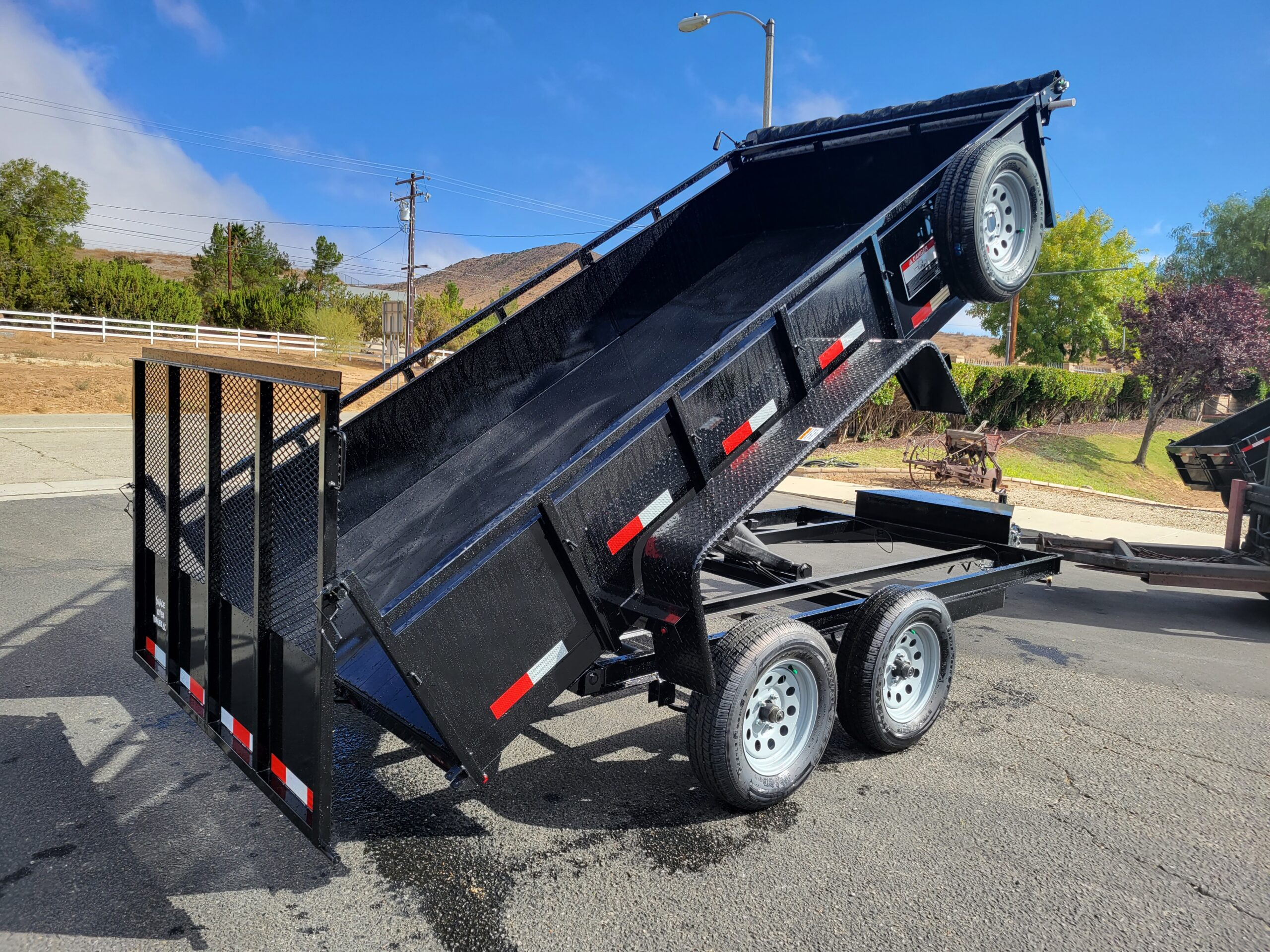 Snake River 6x12.6 Dutility Dump - Passenger side rear 3/4 view bed up w/spreader gate activated