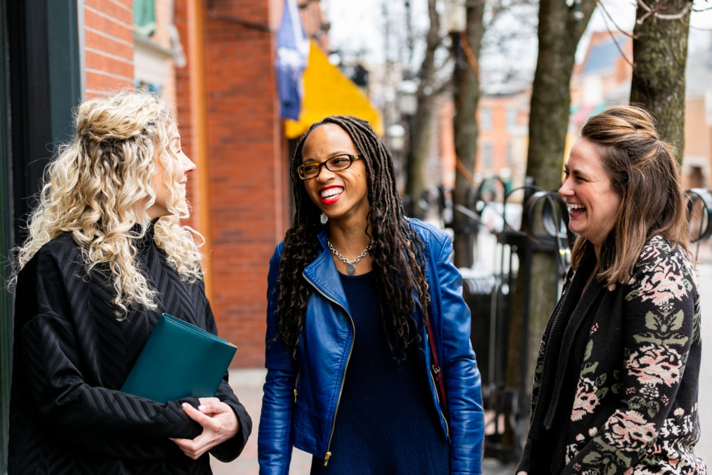 African American woman walking with two Caucasian women on the street, smiling