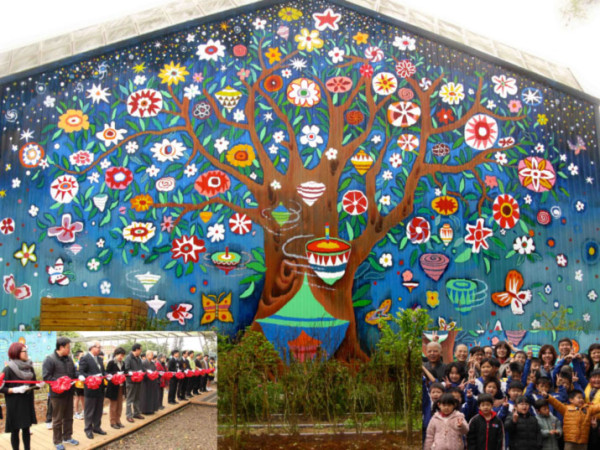 Dedication of the three-story high mural on corrugated metal wall on March 7, 2015. Many distinguished guests participated in the ribbon-cutting ceremony. The small Mei Hua Elementary School, neglected and little visited, was filled with reporters, visitors, and excitement. We accomplished the ambitious project within nine days, with numerous pairs of hands, from that of kindergarteners to senior citizens, families, volunteers from local region and far away cities. We accomplished and WE CAN!!!