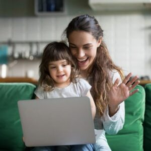 Mother and daughter on smiling at laptop screen