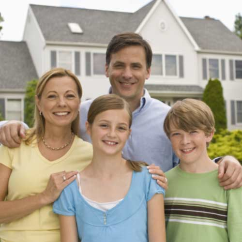 family smiling for photo in front of home