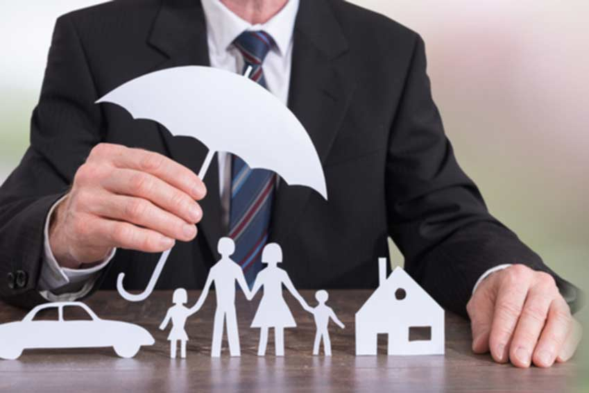 man in suit holding paper umbrella over paper family